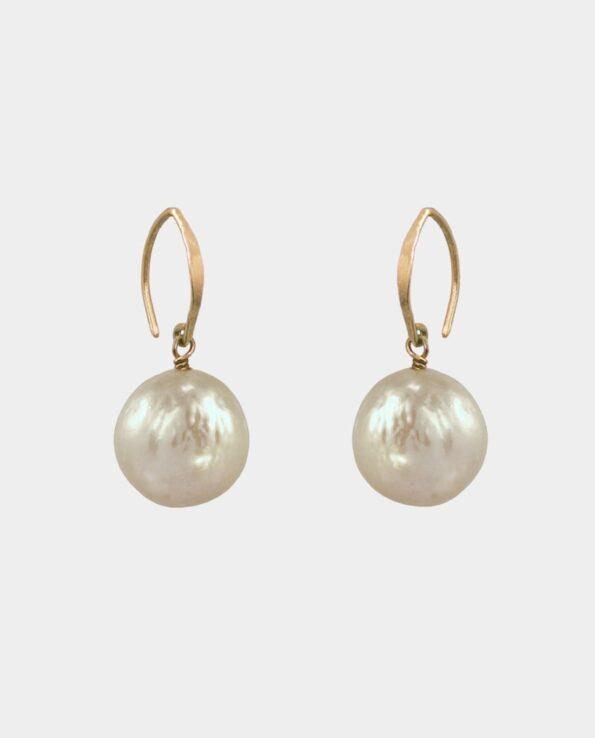 Øreringe med gyldne cirkelrunde perler og spidse rustikke ørekroge som skaber kontrast til ædelmetallets formsprog og udgør et smykke med patina