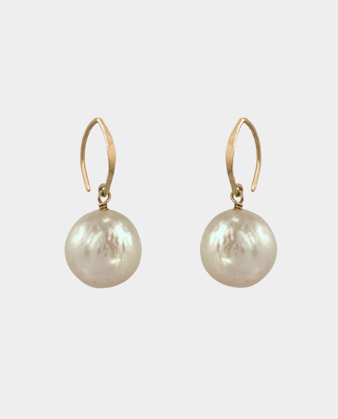 Earrings with golden circular pearls and pointy rustic ear hooks that contrast with the mode of expression of the precious metal and shapes a piece of jewelry with patina