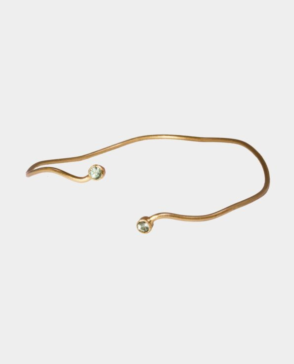 Armbånd med plirrende lysegrønne safirer på sterlingsølvet der er forgyldt med 18 karat guld som snor sig om håndleddet som en slange
