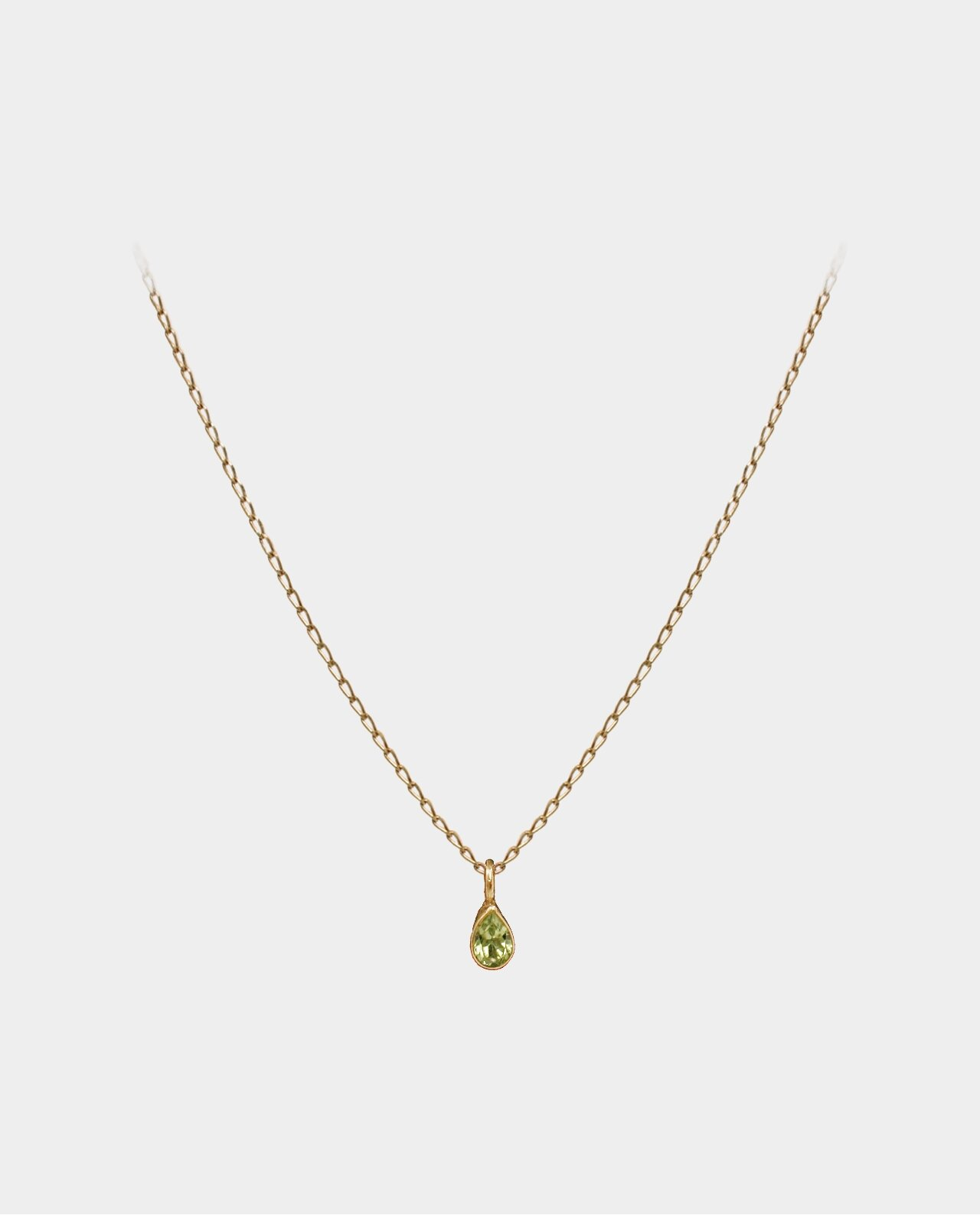 Necklace with blue peridot pendant whose reflections of light in the facets of the jewellery are compelling