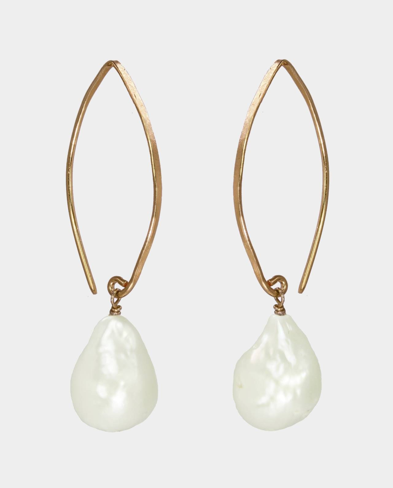 The long curved ear hooks of the earrings and natural-shaped white freshwater pearls are inspired by Gothic cathedrals