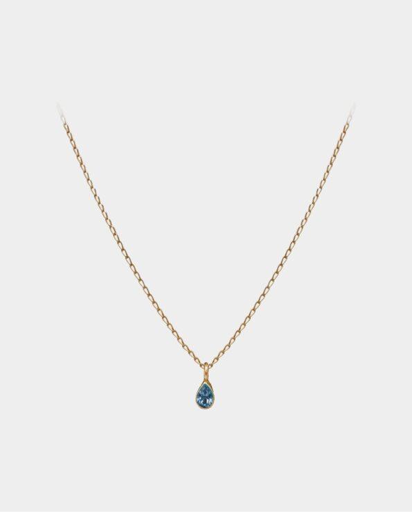 Halskæde med blå topas vedhæng hvis lysreflekser i smykkets facetter virker dragende