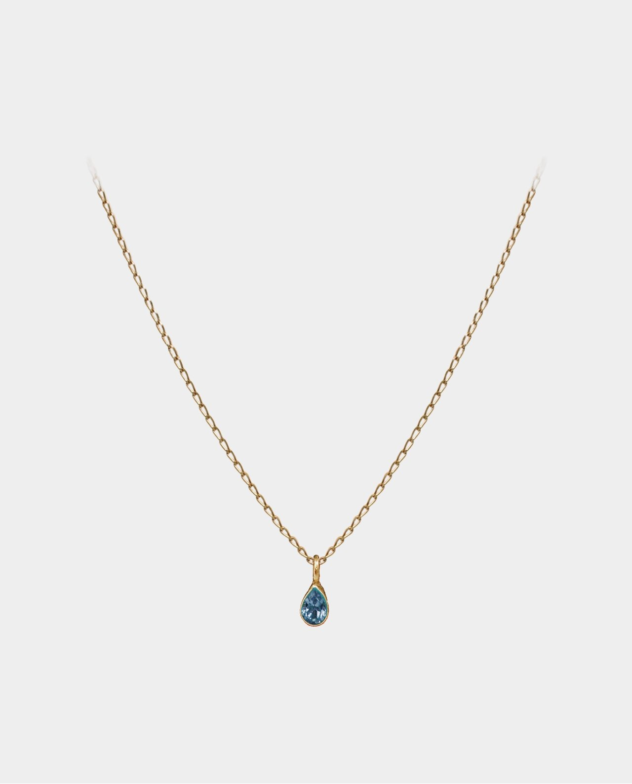Necklace with blue topaz pendant whose reflections of light in the bevels of the jewelry are compelling
