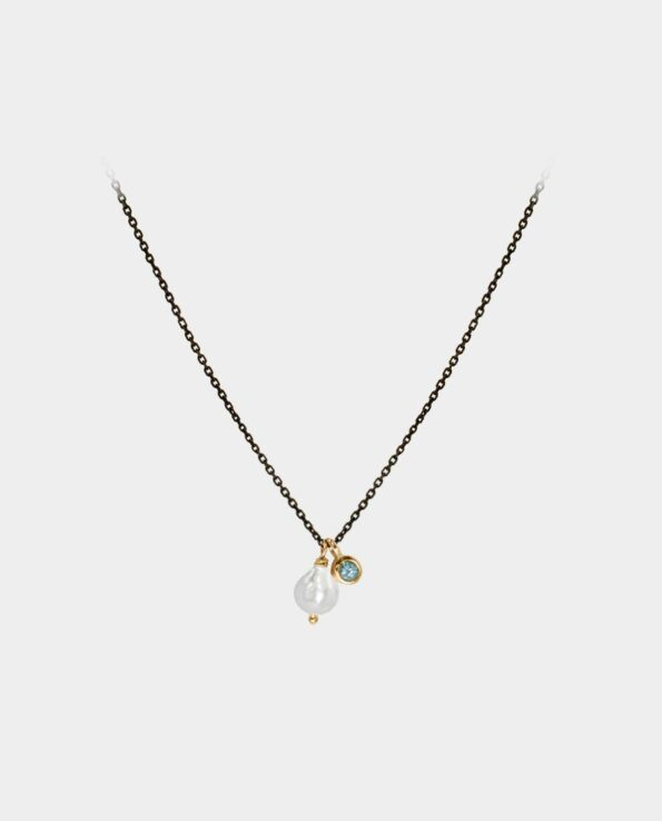 Henrivende halskæde med blå topas og hvid perle i samme vedhæng som et moderne svar på klassisk smykkedesign der gør dig ynderfuld og smart på samme tid
