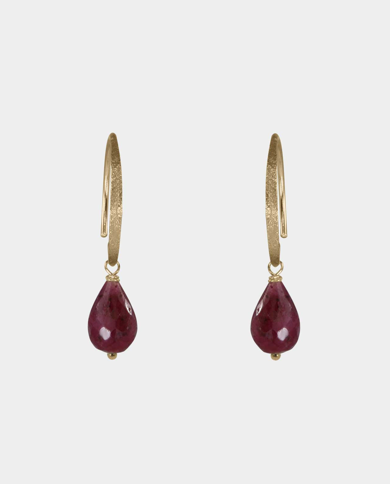 The complete earrings with bevelled burgundy ruby droplets that do not compromise the classic look with its organic and geometric sharpness and therefore every woman's great desire